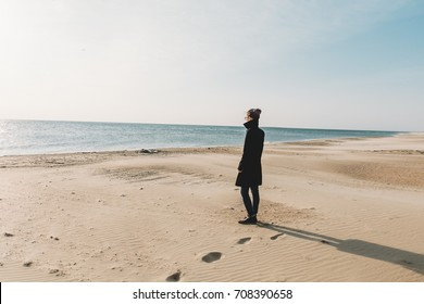 Young woman walking on sandy shore and enjoying view of sea in autumn.