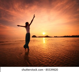 Young woman walking on a sandy beach