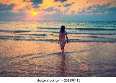 Young woman walking on seashore at sunset and looking at the sun