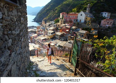 Young woman walking on stairs of small street of Vernazza town. Italy