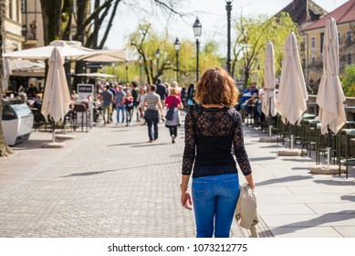 Young woman is walking in on the street in Ljubljana old town,  where all the bars and restaurants are near Ljubljanica river in Ljubljana, Slovenia