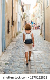 Young woman walking on the street of adriatic town in Croatia. Girl walking on the street of Krk old town on island Krk, Croatia. Travel and holiday concept.