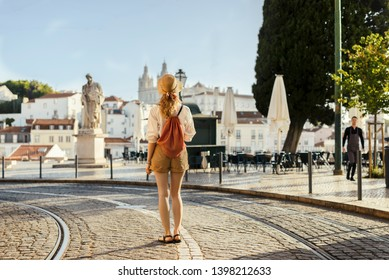 Young woman walking on the street of european southern city wearing safari shorts, white shirt, hat and golden bag