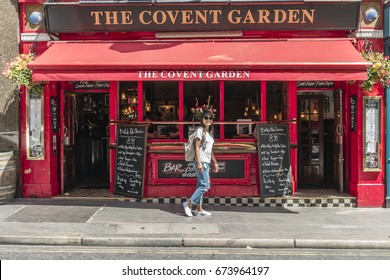 young woman walking on street outside a red Cafe bar restaurant typical English bar at Covent garden London England 23 June 2017 ,Red Bar restaurant at Covent Garden, Red Pub