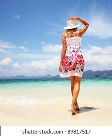 Young woman walking on a warm beach