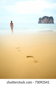 Young woman walking on wet perfect sand and going to swim in a sea