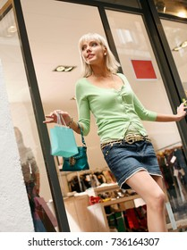 Young woman walking out of shop sale