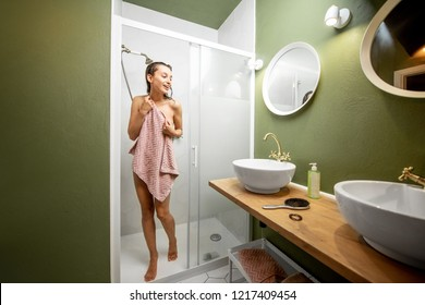 Young woman walking out from the shower cabin covered with a towel in the beautiful loft bathroom interior
