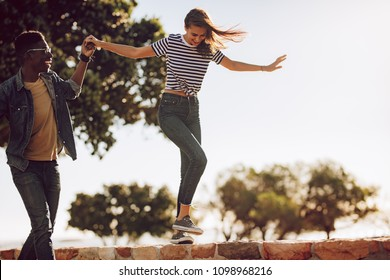 Young woman walking over a embankment while holding hand of a friend. Best friends having a great time together outdoors.