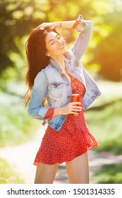 Young woman walking in park. Beauty nature scene with colorful background. Fashion woman with bottle of drink relax at summer season. Outdoor lifestyle. Happy smiling woman in red dress