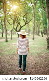 young woman walking in a park with sunshine.