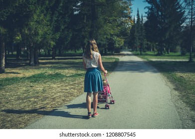 A young woman is walking in a park with a toddler in a pushchair