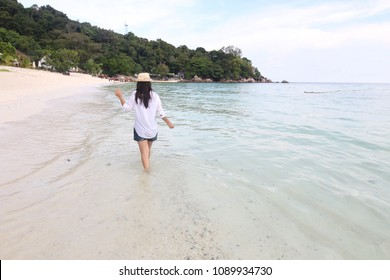 Young Woman walking and play on the beach wearing a hat and white shirt relax travel with nice sea sand and clear bluesky background.Concept travelers in beautiful nature landscape koh lipe Thailand.