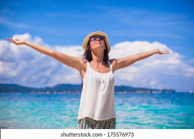 Young woman walking spread her hands on white sandy beach