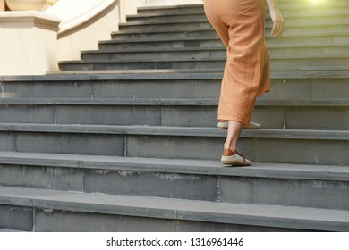 Young woman walking up the stairs with morning sun background.