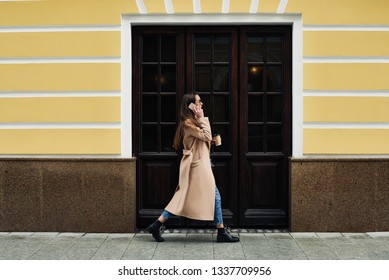 Young woman walking the street, with a coffee to go and a cell phone.