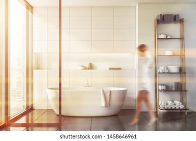 Young woman walking in stylish bathroom interior with white tile walls, gray tile floor, comfortable white bathtub and shelves with towels and shampoos. Toned image blurred