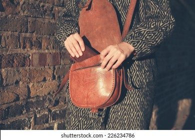 A young woman is walking at sunset and is getting her wallet out of her bag