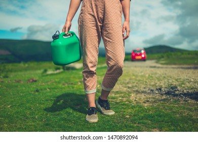 A young woman is walking in ther wilderness with a can of gas