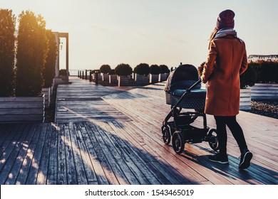 ベビーカーと一緒に市の公園を歩く若い女性。戸外での活動のための暖かい秋や春の天気。美しい都市建築と景観デザイン。日没、空に雲、晴れた日、歩く