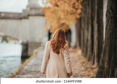 Young woman walking through Paris streets. Walking  on promenade