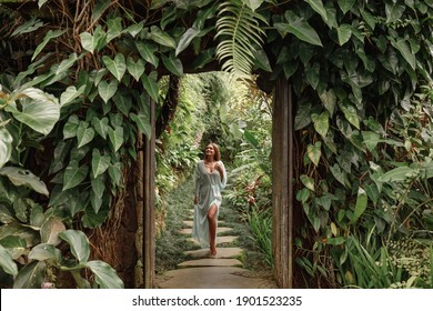 Young woman walking in tropical garden in long summer dress, greenery and palm trees around, enjoying nature