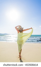 young woman walking to the water on the beach
