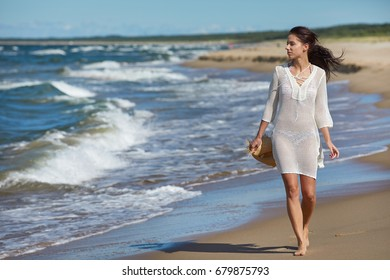 Young woman walking in water wearing white beach  dress