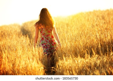 Young woman walking in wheat field on sunset