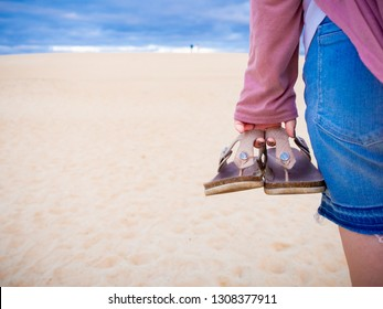 Young woman walkong along the beach with flip-flops in her hand