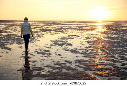 A young woman walks across the mudflats of the Waddensea at low tide, Holland