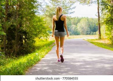 Young woman walks alone on a road outdoor