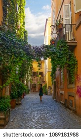 A young woman walks alone through a picturesque back alley in the Trastevere district or Rome, Italy