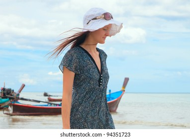 young woman walks along the beach in Thailand