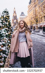 A young woman walks at Christmas in the square near the decorated Christmas trees. Candy is a lollipop in the form of a heart. Tinting