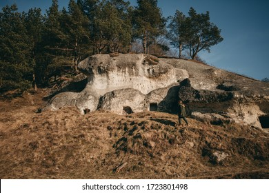 Young woman walks in green clothes, coat in nature near the old house in the rock near Lviv in Ukraine. Settlement of white Croats. Stilskoe settlement. Stil'ske Horodyshche, Stil's'ko