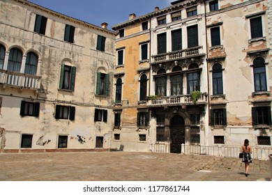 A young woman walks through a square surrounded by beautiful architecture in Venice with amazing rusty buildings, balconies and traditional design.