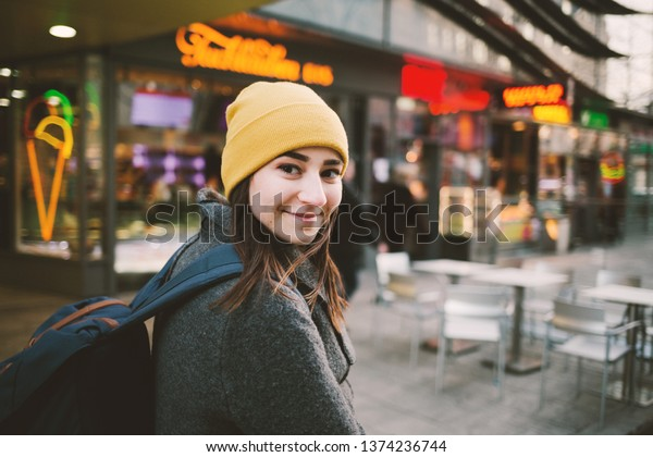 Young woman walks through a street with neon signs. Travel,lifestyle and youth concept.