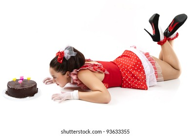 A young woman wants to eat cake on the floor.