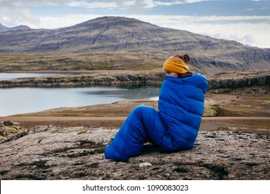 Young woman in warm blue sleeping bag ,  on the stones with northern mass, Iceland