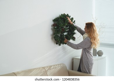Young woman in warm clothes hanging Christmas wreath on wall in her apartment