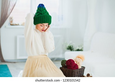 Young woman in warm hand knitted hat at home. Pretty lady in big green cap, smiling happily. Beautiful girl knitting in cozy flat wearing casual clothes. Horizontall shot. Copy space