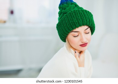 f8154dff6f9 Young woman in warm hand knitted hat at home. Pretty lady in big green cap