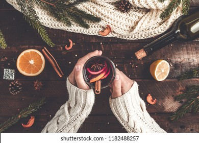 A young woman in a warm, knitted, white pullover is holding a Christmas, hot mulled wine in a glass with spices and citrus fruits. A cozy, winter evening. Winter drinks. Flat lay, top view