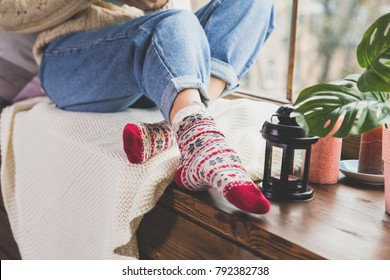 Young woman in warm knitted woolen sweater and blue denim jeans  sitting on the window sill. Woman legs in colorful socks on the white knitted woolen blanket