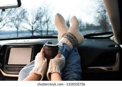 Young woman in warm socks holding her legs on car dashboard and drinking coffee. Cozy atmosphere