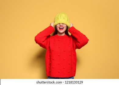 Young woman in warm sweater and knitted hat on color background. Celebrating Christmas
