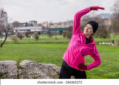 Young woman warming up and stretching the upper body and arms before running on a cold winter day in an urban park.