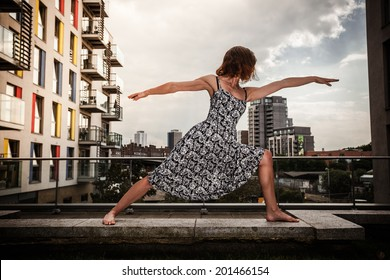 A young woman is in a warrior yoga pose on a roof top in the city