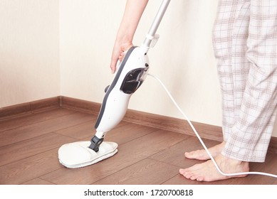 A young woman washes the floor with a modern steam cleaner. Cleaning of the apartment with the help of modern technology